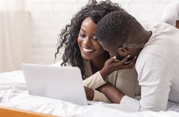 Cheeful african american couple relaxing on bed with laptop - Stock Photo - Images
