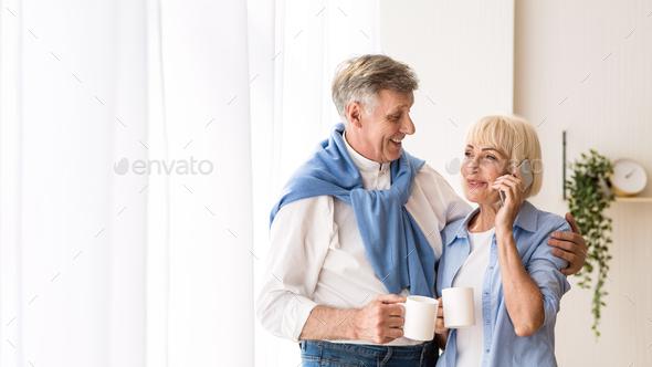 Happy senior woman talking on phone near window, free space - Stock Photo - Images