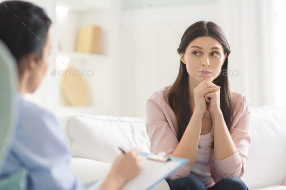 Interested young woman listening carefully to psychotherapist - Stock Photo - Images