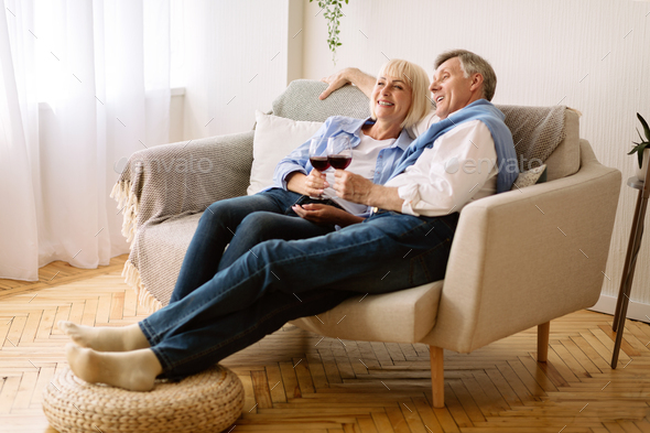 Happy retirement. Senior couple drinking wine and watching tv - Stock Photo - Images
