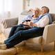 Happy retirement. Senior couple drinking wine and watching tv - PhotoDune Item for Sale