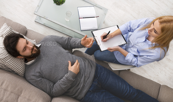 Depressed man discussing his inner fears with psychologist - Stock Photo - Images