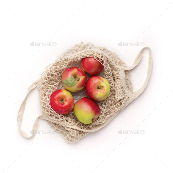Ripe apples in eco cotton string bag and on white - Stock Photo - Images