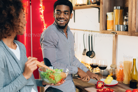 Vegetarian african-american couple cooking salad in kitchen - Stock Photo - Images