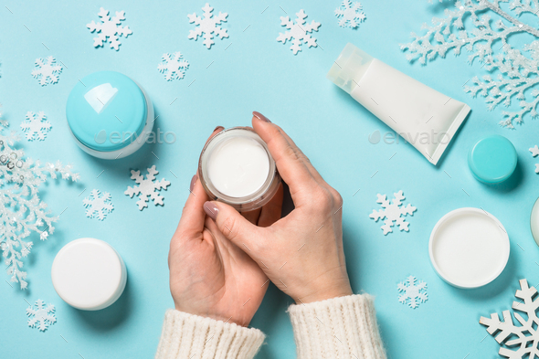 Woman using winter cream on blue - Stock Photo - Images