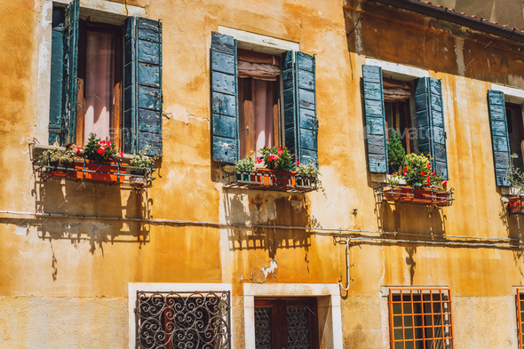 Venice old yellow facade of house with wood windows on the street in Venice Italy - Stock Photo - Images