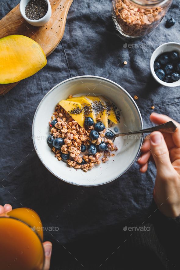 Girl holds a breakfast bowl with crunchy granola - Stock Photo - Images