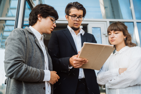 Business team two men and woman working together outside - Stock Photo - Images