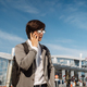 Young man talking on smartphone outdoors. Communication concept. Front view - PhotoDune Item for Sale