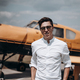 A man standing on the background of a small single engine plane - PhotoDune Item for Sale