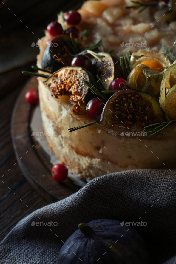 Cheesecake with physalis and dates on a wooden stand - Stock Photo - Images