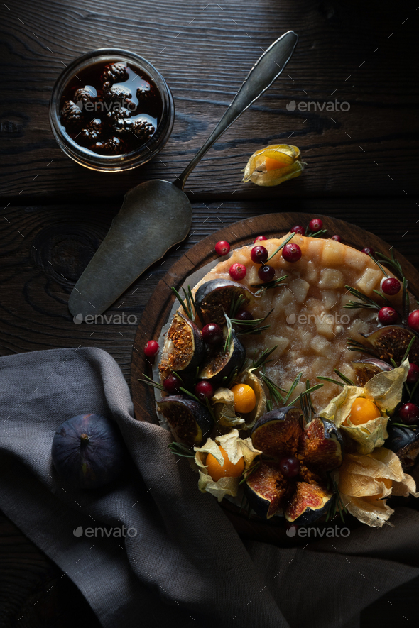 Cheesecake with dates and physalis on a stand with a napkin - Stock Photo - Images