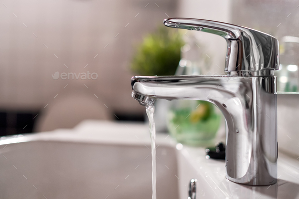 Cold water flowing from faucet in clean bright bathroom - Stock Photo - Images