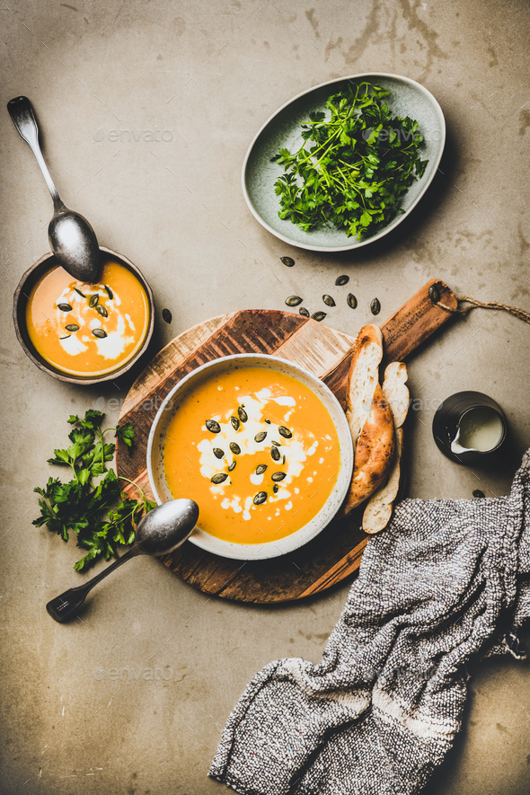 Flat-lay of pumpkin cream soup with seeds, parsley and cream - Stock Photo - Images