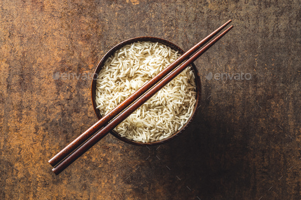 Uncooked indian long rice in bowl and chopsticks. - Stock Photo - Images