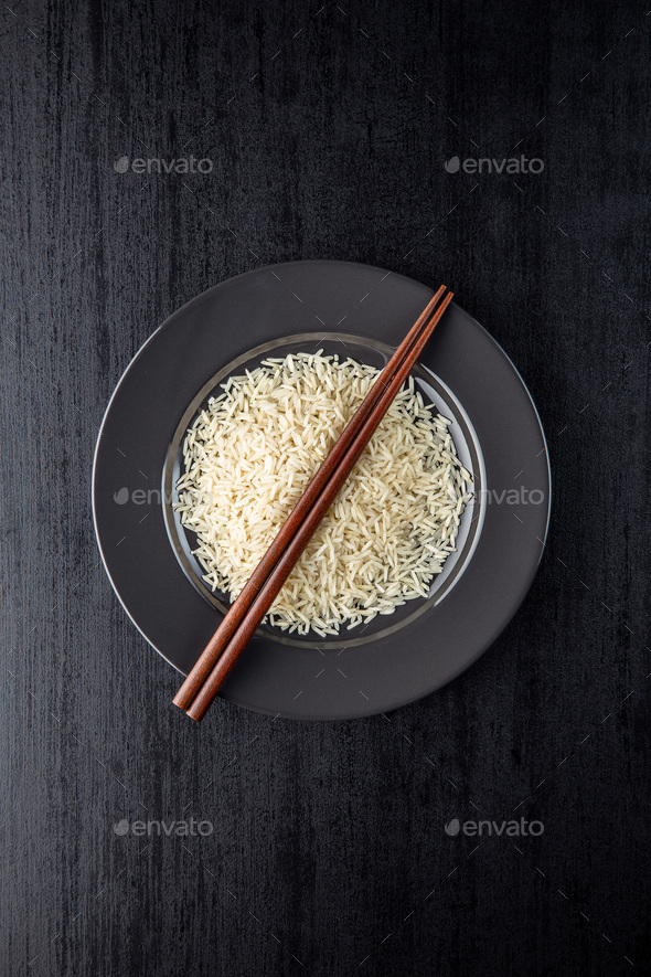 Uncooked indian long rice on plate and chopsticks. - Stock Photo - Images