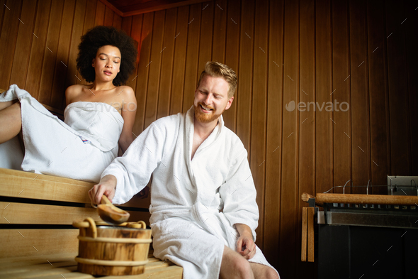 Happy couple having a steam bath in a sauna - Stock Photo - Images