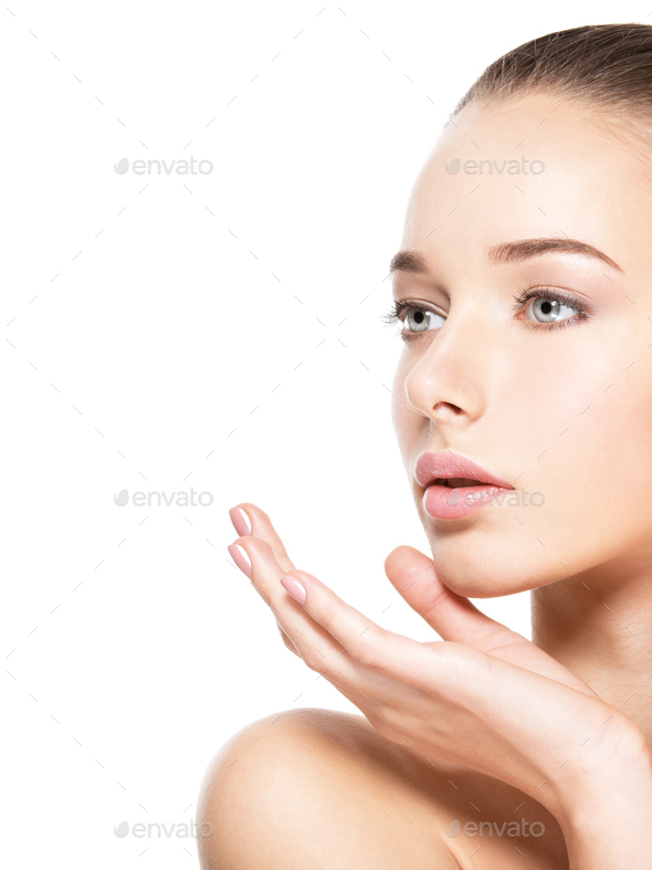 Young woman with healthy clean skin touches the face. Skin care concept. - Stock Photo - Images