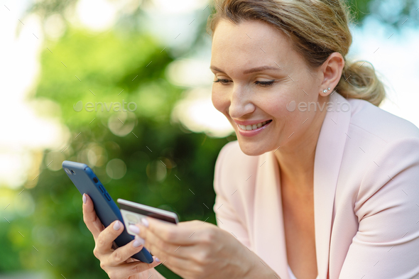 Businesswoman with a credit card and phone makes purchasing outdoors. - Stock Photo - Images