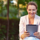 Smiling businesswoman with a tablet in the park. - PhotoDune Item for Sale