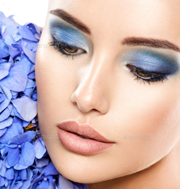 Closeup face of young beautiful woman with a blue makeup of eyes. - Stock Photo - Images