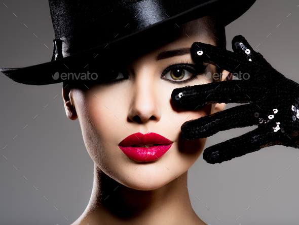 Сlose-up portrait of a woman in a black hat and gloves with red lips - Stock Photo - Images