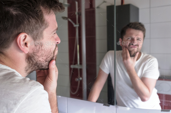 Man check condition of his skin in mirror reflection at the bathroom - Stock Photo - Images