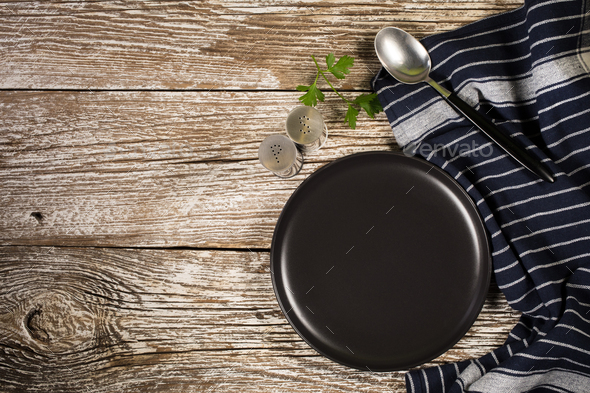 Black plate, spoon and napkin. - Stock Photo - Images