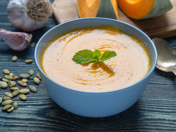 Creamy soup of pumpkin with mint on dark blue wooden background, garlic, slices of pumpkin - Stock Photo - Images