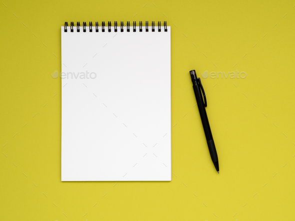 open notepad on the spiral with a clean white page and pencil on a bright yellow background color - Stock Photo - Images