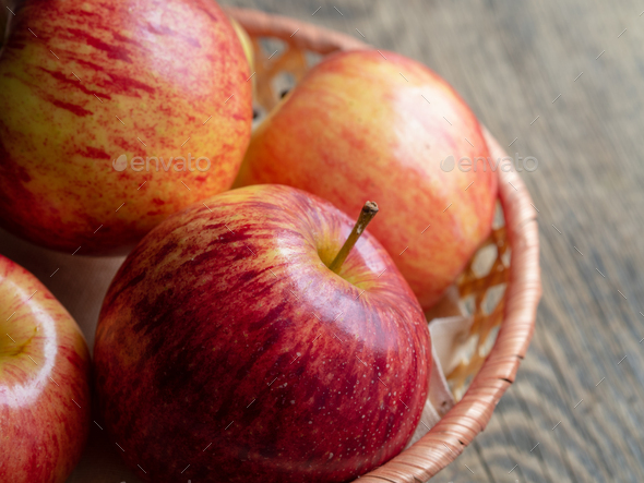 ripe juicy red apples in a basket on a wooden table, close up - Stock Photo - Images
