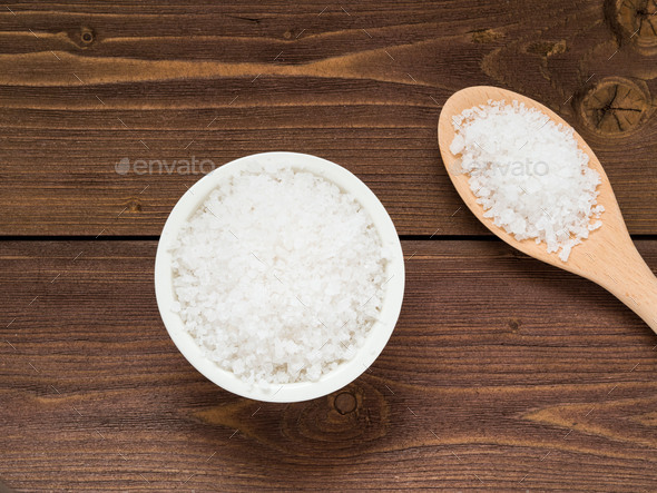 White bowl with large sea salt and wooden spoon - Stock Photo - Images