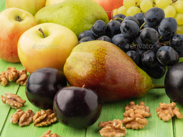 set of fruits on a green wooden table - apples, pears, grapes, plums, walnuts - Stock Photo - Images