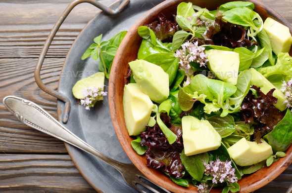 Top view at clay dish with salad of avocado, green and violet lettuce - Stock Photo - Images