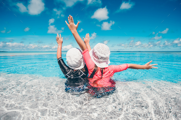 Adorable little girls playing in outdoor swimming pool on vacation - Stock Photo - Images