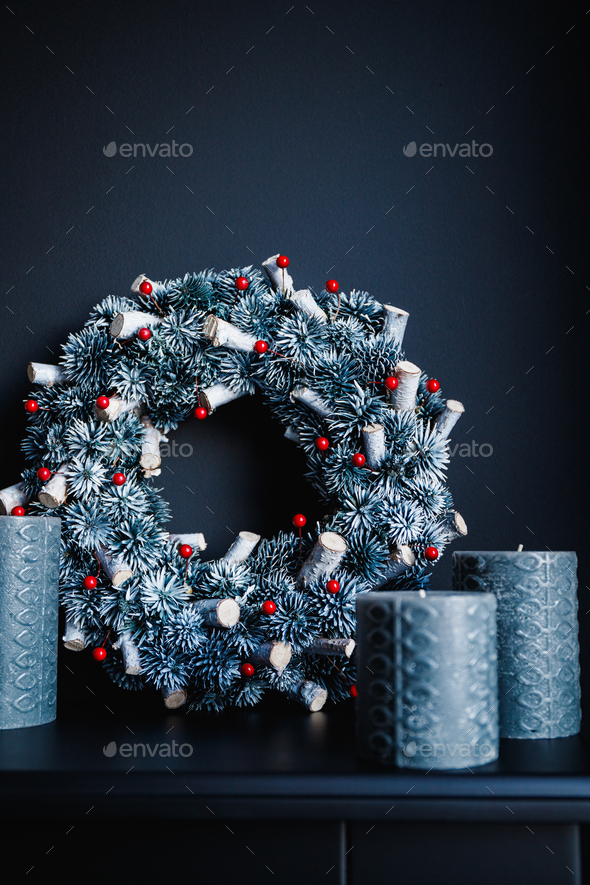 Grey candles and Christmas wreath on a decorative fireplace against black wall - Stock Photo - Images