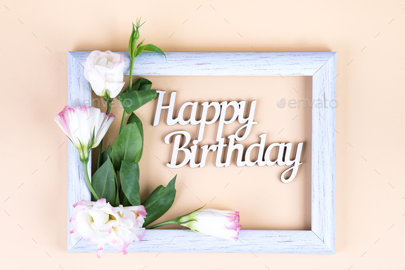 Empty white frame and flowers eustoma on beige paper background with copy space. Birthday concept - Stock Photo - Images