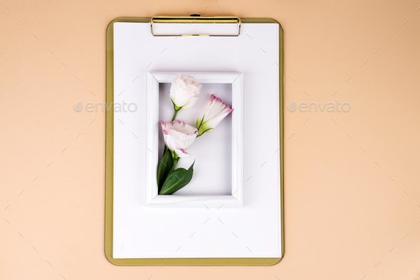 Clipboard with eustoma flower and white frame on beige paper background, flat lay. Post card mockup - Stock Photo - Images