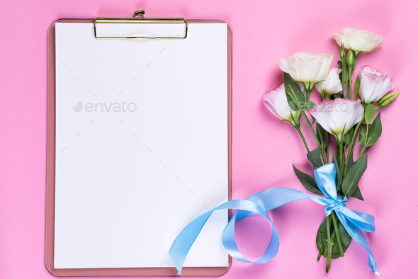 Minimal composition with a Eustoma flowers in an envelope with clipboard on a pink background, top - Stock Photo - Images