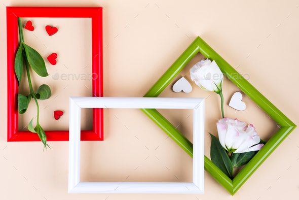 Empty frame and flowers flat lay on beige paper background with copy space. Holiday concept - Stock Photo - Images