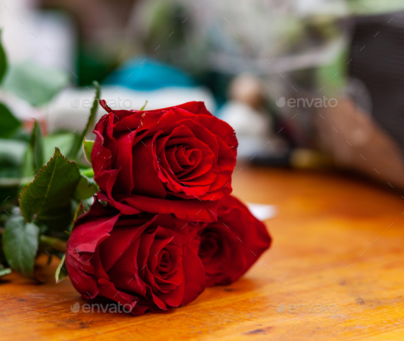 Red roses are on the counter in the flower shop. - Stock Photo - Images