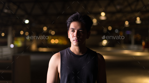 Portrait of young handsome Asian man thinking outdoors at night - Stock Photo - Images