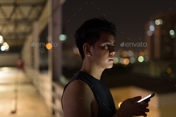 Young handsome Asian man thinking while using phone against view of the city at night - Stock Photo - Images