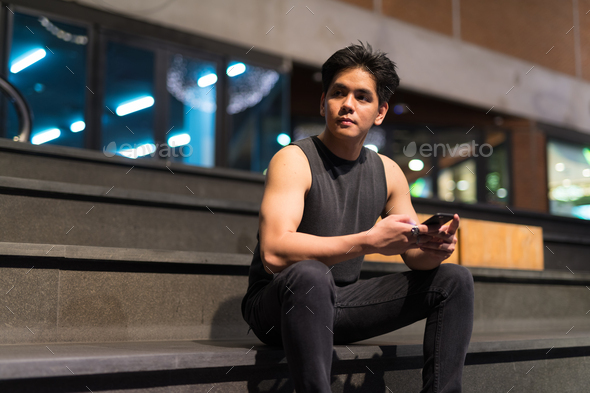 Young handsome Asian man thinking while using phone in the city outdoors at night - Stock Photo - Images