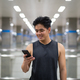 Young happy Asian man using phone at the subway station - PhotoDune Item for Sale