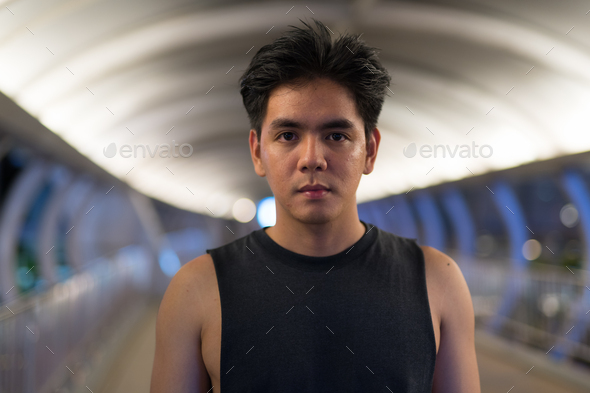 Portrait of young handsome Asian man outdoors at night - Stock Photo - Images