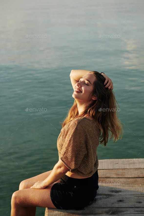 Woman sitting on wooden pier - Stock Photo - Images