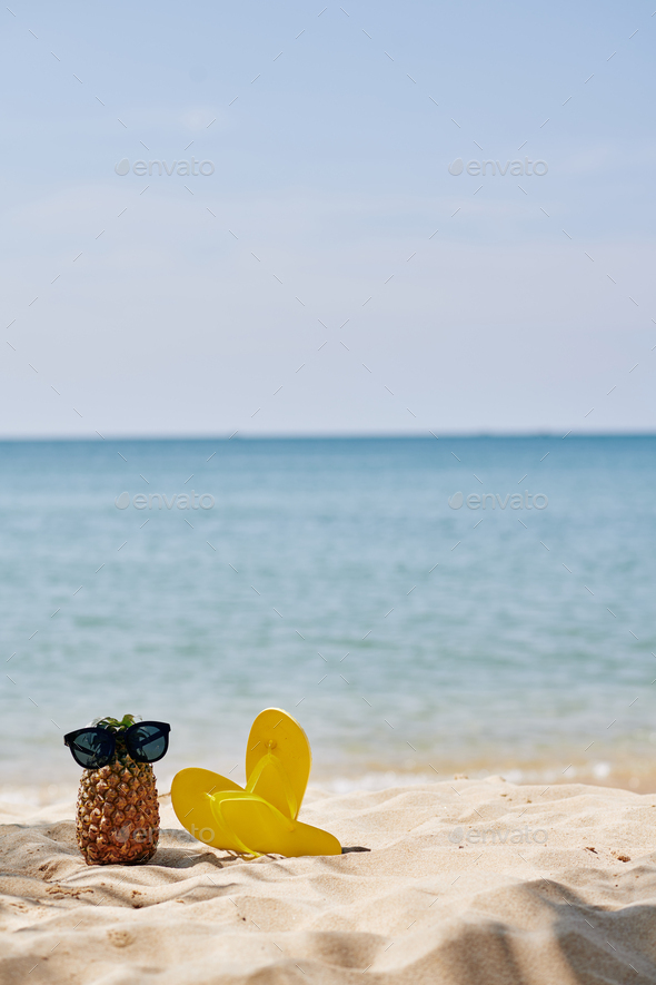 Flip-flops and pineapple on beach - Stock Photo - Images