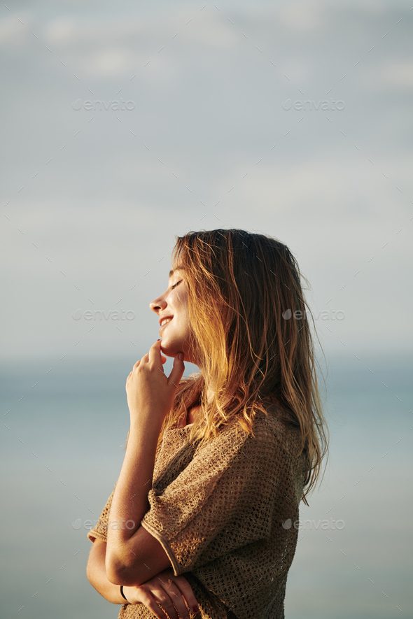 Woman standing in sunset sun rays - Stock Photo - Images