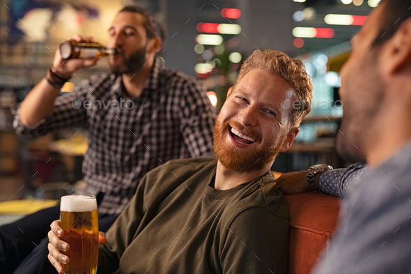 Friends laughing and drinking draft beer - Stock Photo - Images
